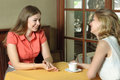 Two women talking in the cafe girls at a table girls drink cherry juice sitting by window Royalty Free Stock Photography