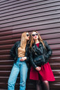 Two Women Talking in the City.Outdoor lifestyle portrait of two best friends hipster girls wearing stylish Leather Royalty Free Stock Photo