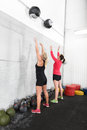 Two women throws medicine balls in fitness gym young team throw at a wall center Royalty Free Stock Photos