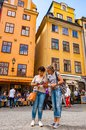 Two women tourists checking the guide on cozy medieval street with walking people, yellow buildings facades in Gamla Stan, Old