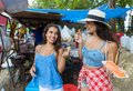 Two Women Tourists Eat Fresh Fruits Happy Smiling Walking Streets In Asian City Young Attractive Girls On Vacation Royalty Free Stock Photo