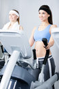 Two women training on simulators in gym young sports wear Royalty Free Stock Photography