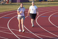 Two women walking a track Royalty Free Stock Photo