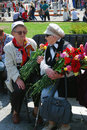 Two women war veterans speak to each other sitting on a bench holding flowers victory day celebration on may in moscow Stock Images