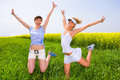 Two women in white clothes jumping in field Royalty Free Stock Images