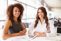Two women working at an architect?s office looking to camera Royalty Free Stock Photo
