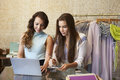 Two women working in a clothes shop using a laptop computer Royalty Free Stock Photo