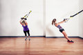 Two women working out with straps young are doing bodyweight exercises Royalty Free Stock Images