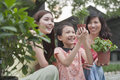 Two women and young girl smiling and gardening holding plants Royalty Free Stock Photos