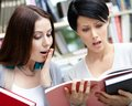 Two wondered students read at the library beautiful female books Royalty Free Stock Image