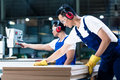 Two wood workers in carpentry cutting boards Royalty Free Stock Photo