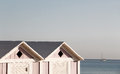 Two wooden bathing boxes and a sailing boat Royalty Free Stock Photo