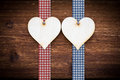 Two wooden hearts on dark wood planks