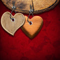 Two wooden hearts on red floral background hanging from a section of tree trunk velvet with roses flowers Stock Image