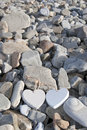 Two wooden hearts on a rocky beach love the rocks of Royalty Free Stock Photography