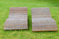 Two wooden lounge sunbeds standing on green grass in park Royalty Free Stock Photo