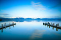 Two wooden pier or jetty and on a blue lake sunset and sky refle cloudy reflection water long exposure versilia massaciuccoli Royalty Free Stock Photo