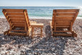 Two wooden sun loungers stand on the adriatic sea beach in montenegro Stock Images