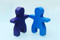 Two wooden toy people hand in hand meet each other friendly Stock Image