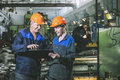 Two workers at an industrial plant with a tablet in hand, workin