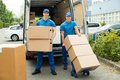 Two workers loading cardboard boxes in truck happy male stack of Stock Photos