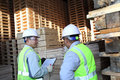 Two workers talking beside on stacking pallet Royalty Free Stock Photo
