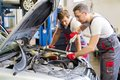Two workers in a workshop mechanic fixing car Stock Images