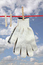 Two working gloves clothesline over blue sky Stock Photo