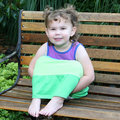 Two year old baby girl on a park bench Stock Photo