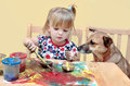 Two year old girl painting a little at the table with her dog sitting next to her Stock Photos