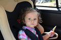 The two-year-old girl sits in the car in a baby car seat