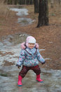 Two years old girl playing in icy puddle