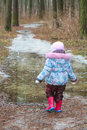 Two years old girl walking on icy puddle Royalty Free Stock Photo