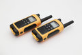 Two yellow and black portable radio set on the light background concept of wireless communications Royalty Free Stock Photos