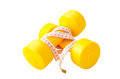 Two yellow dumbbells and tape measure isolated on the white back Royalty Free Stock Photo