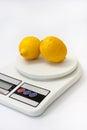 Two yellow lemons on white kitchen digital scale Royalty Free Stock Photo