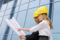 Two young architects on construction site or designers handsome asian men and beautiful blond european women image is Royalty Free Stock Image