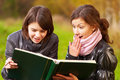 Two young attractive women reading a book Stock Photo