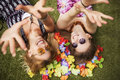 Two young beautiful blonde hipster girls on summer day having fun in european city. Green grass on a background and flower leafs.