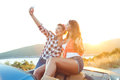 Two young beautiful girls are doing selfie in a convertible Royalty Free Stock Photo