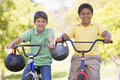 Two young boys on bicycles outdoors smiling Royalty Free Stock Image