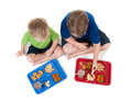 Two young boys eating school lunch on white Stock Photography