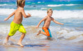Two young boys having fun on tropcial beach tropical happy best friends playing Stock Photo