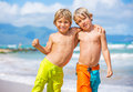 Two young boys having fun on tropcial beach tropical happy best friends playing Stock Images