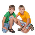 Two young boys are sitting together on the white background Royalty Free Stock Photography