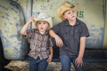 Two young boys wearing cowboy hats leaning against antique truck an in a rustic country setting Stock Image