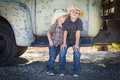 Two young boys wearing cowboy hats leaning against antique truck an in a rustic country setting Stock Photography