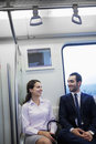Two young business people sitting and chatting on the subway Royalty Free Stock Photo