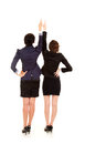 Two young business women standing back and pointing up white background Stock Photography
