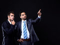Two young businessman showing empty copyspace on black background Stock Photography